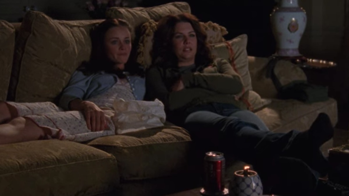 Rory and Lorelai sit on their couch at home, watching TV in 'Gilmore Girls.'