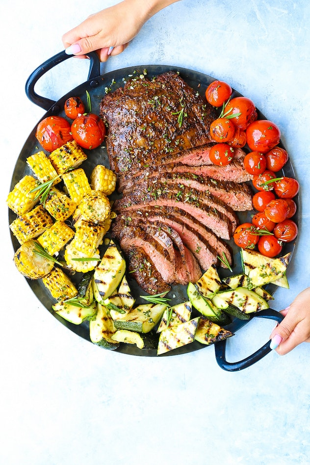 A big plate of grilled sliced flank steak and vegetables.