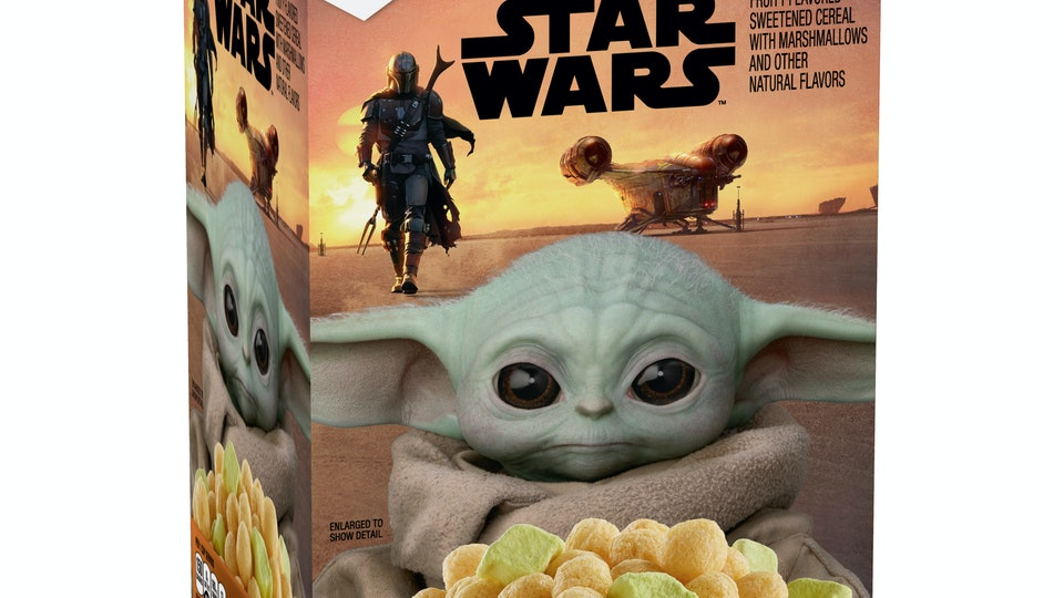 """A two pound box of cereal called """"The Mandalorian,"""" with Baby Yoda on the front looking lovingly at the cereal."""