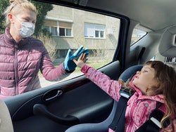 A grandmother and grandchild touch hands on either side of a car window