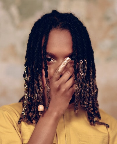 Koffee stands with her hand over her face.