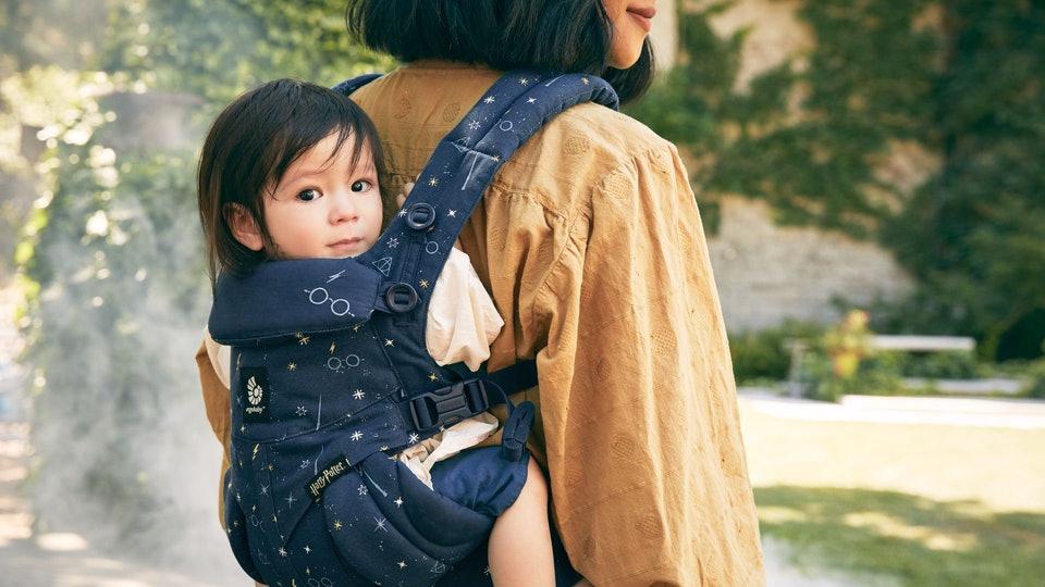 A picture of a woman with a baby in a front facing carrier with Harry Potter imagery on the front.