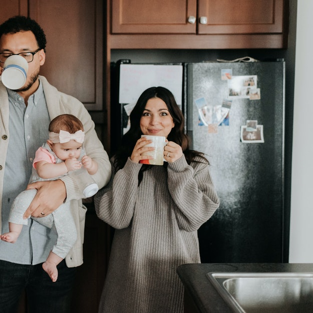 A mother and father sip coffee while holding a baby n their kitchen