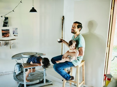 Dad sitting on stool with child, and second child hiding under table