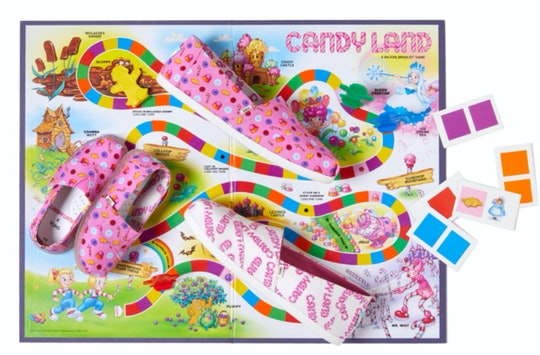 Toms shoes with Candyland prints laying on top of a Candyland board game