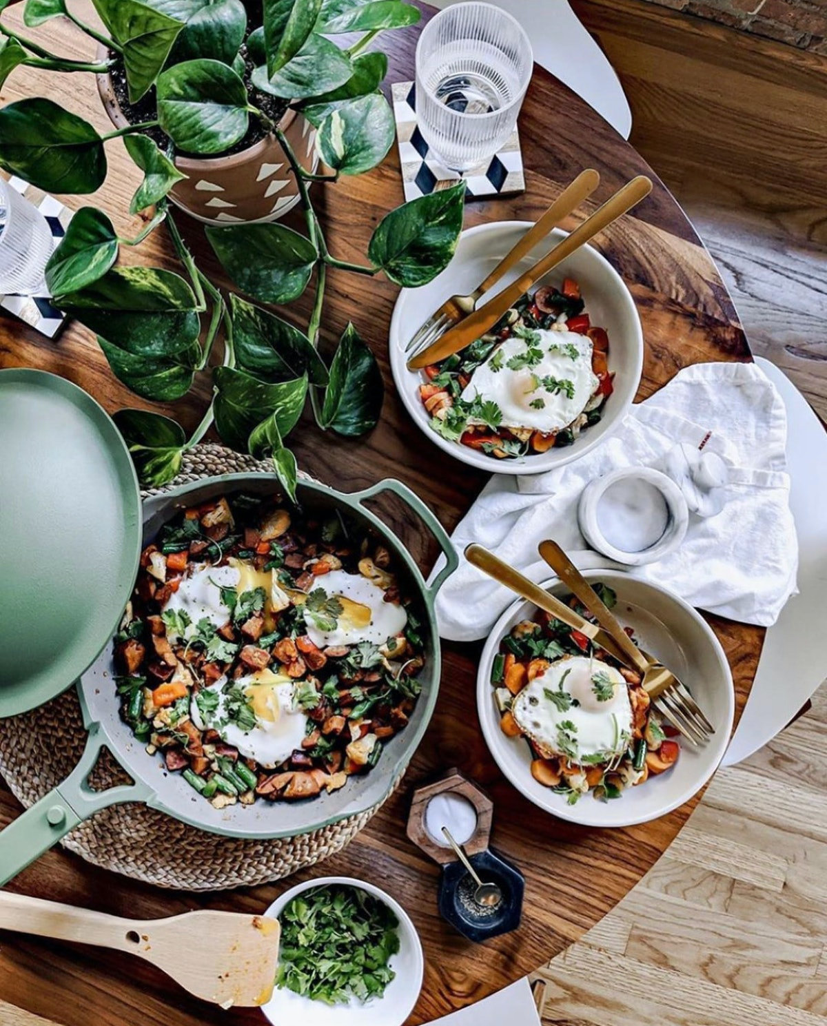 A colorful summer dinner is served on a wooden table in teal Our Place cookware.
