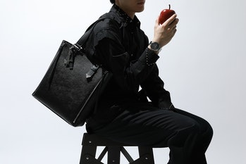 A man can be seen wearing a black shirt with black pants, holding a black bag and apple. His wrist prominently features SuperGroupies' Death Note watch.