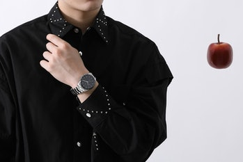A model can be seen wearing a wrist watch with a black shirt on. An apple is placed next to him.