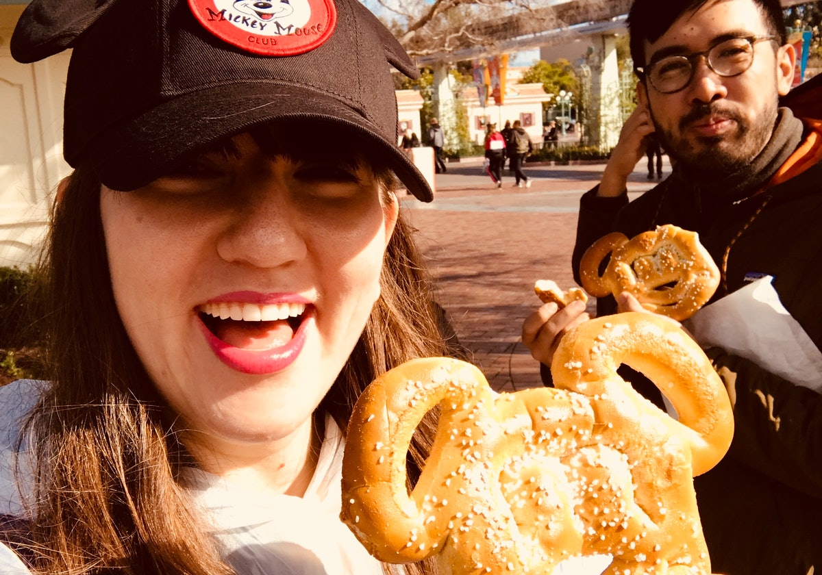 Happy friends hold up their Mickey Mouse pretzels at Disneyland.