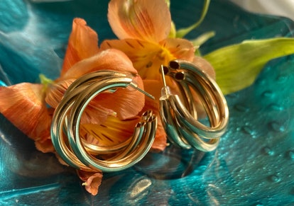 Gold hoop earrings with flowers on a glass dish
