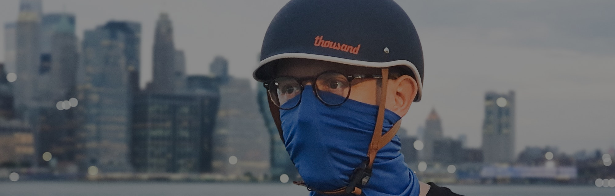 A man in a bicycle helmet with a buff over his mouth and nose standing in front of the Manhattan skyline.
