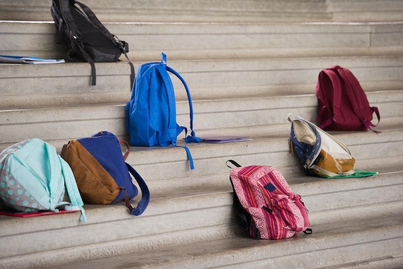 Backpacks rest on school steps. Teachers explain the debate around school reopening.