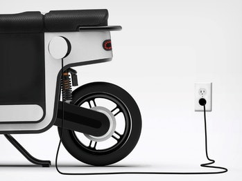An electric scooter plugged in to charge.