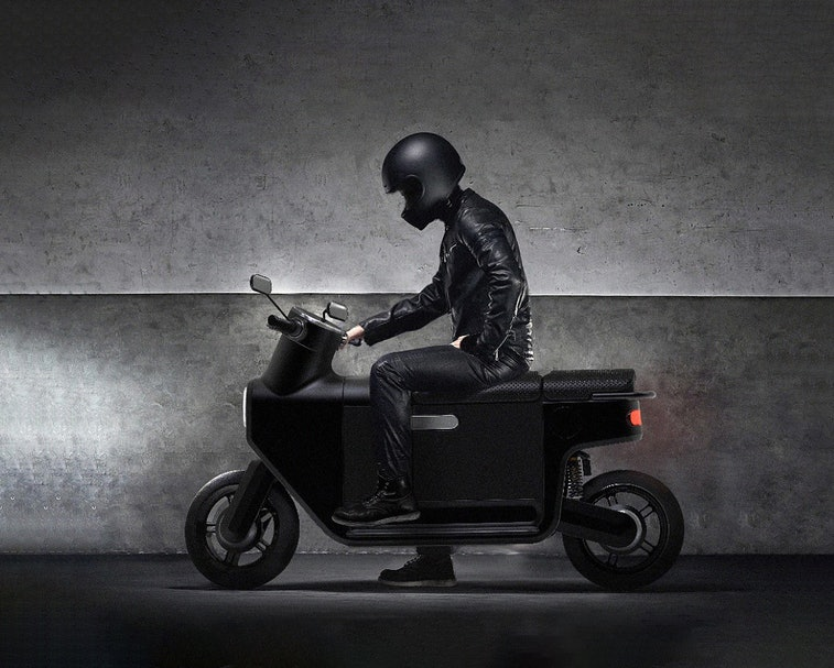 A person wearing all black sitting on a black scooter.