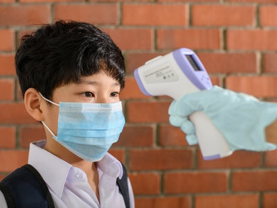 boy with face mask and backpack getting his forehead temperature taken