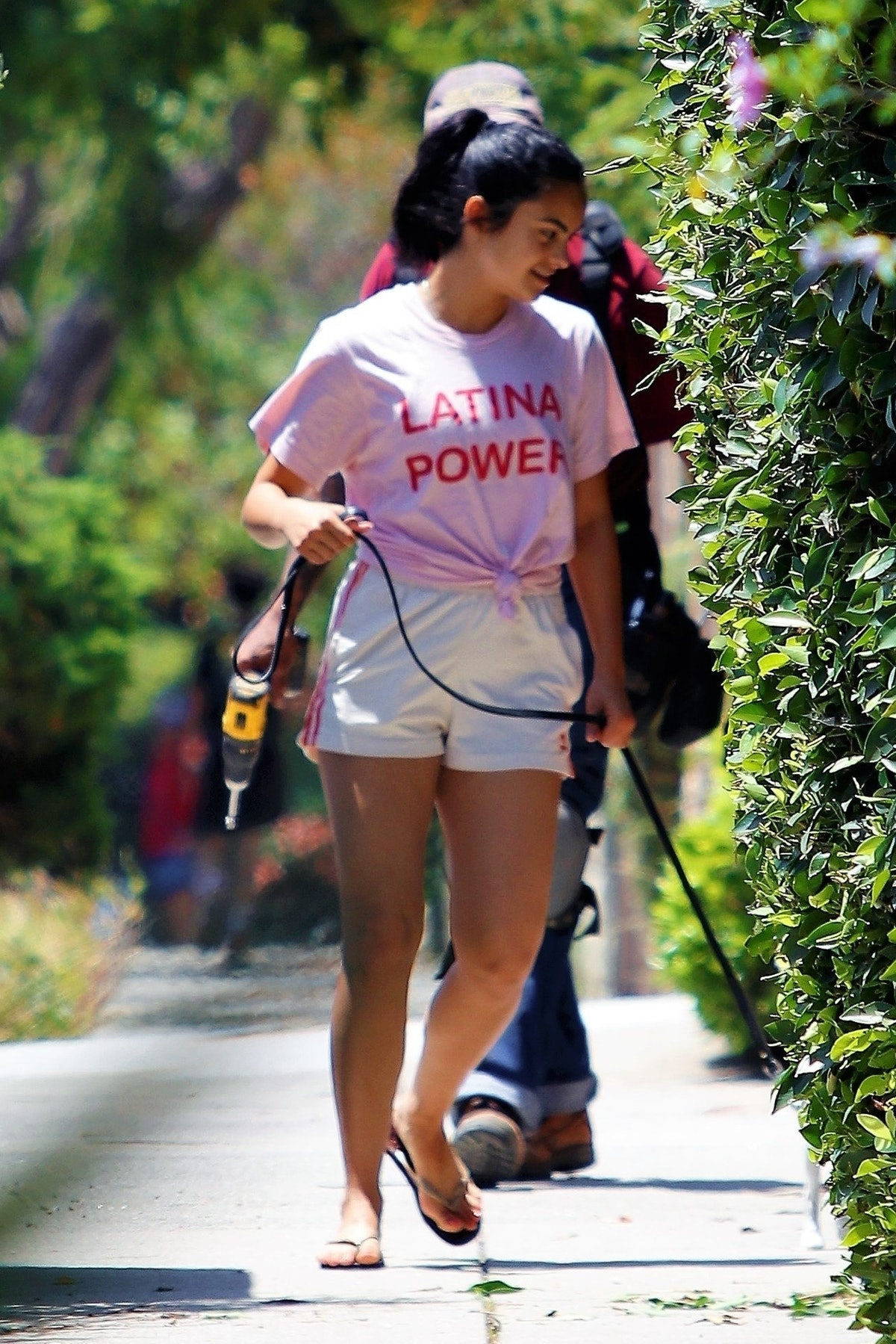 Camila Mendes wearing athletic shorts and a pink T-shirt.