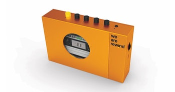 "An orange-colored retro-styled cassette player can be seen with five buttons. Inside the player, there is a cassette while the logo on the product reads, ""We Are Rewind.'"""