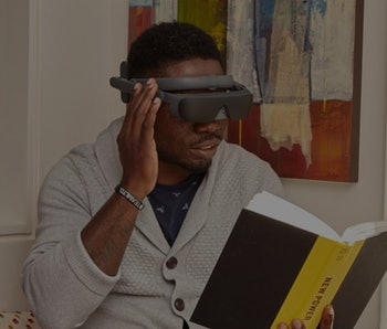 Man reading a book wearing an eSight 4 visual assistance headset.