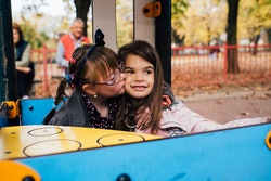 Little girl with Down syndrome hugging and kissing her best friend .