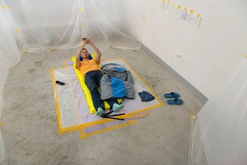 The artist Vincent Tanguy is shown in an orange shirt and jeans on the ground of a live cement house. His walls are made up of plastic sheets. He has a jacket on the ground and blue slippers nearby.