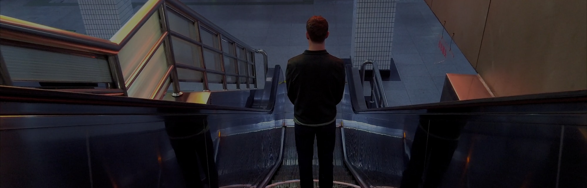 The artist is seen standing on an escalator heading downward. His hands are held in front of him. He has a circle hoop around his feet.