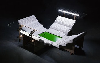A sports stadium made up of keyboard stands and a green screen for a field can be seen. It has typical stadium lights turned on and glaring on the field.