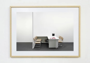 A sterile white room can be seen. It has six beige chairs place in line around a white table.
