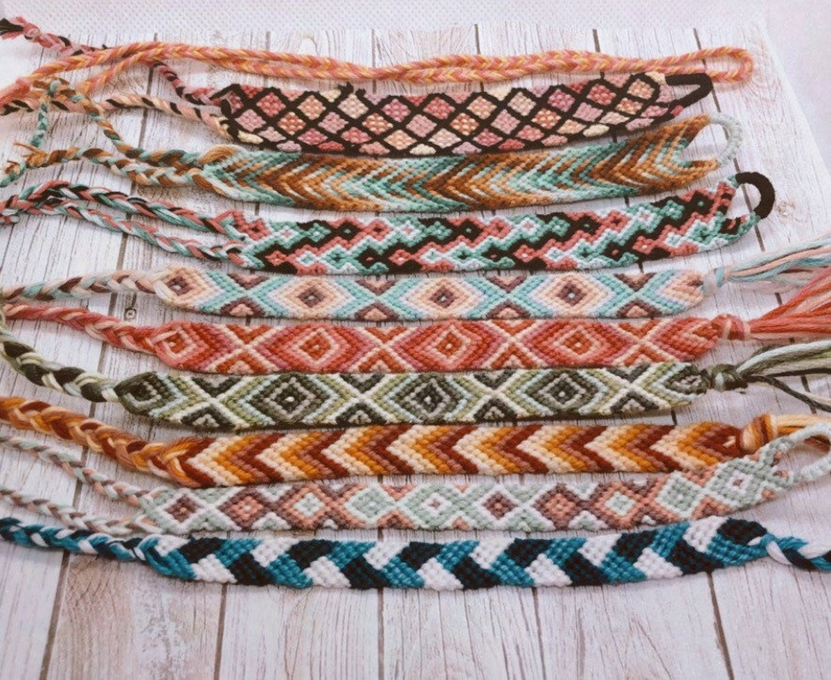 A bunch of homemade friendship bracelets lay on the wood floor.