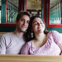 A transnational couple affected by COVID cuddle in happier times.