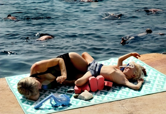 a mother and child rest on a blanket on a dock