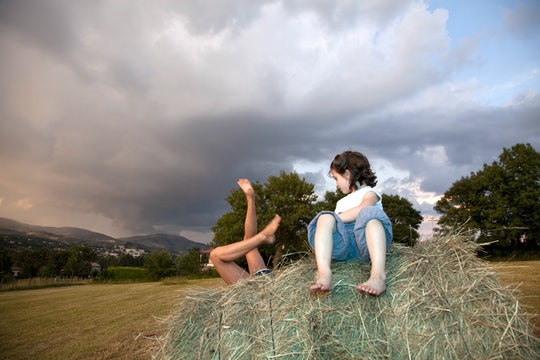 Two girls play on a bale of hay in France