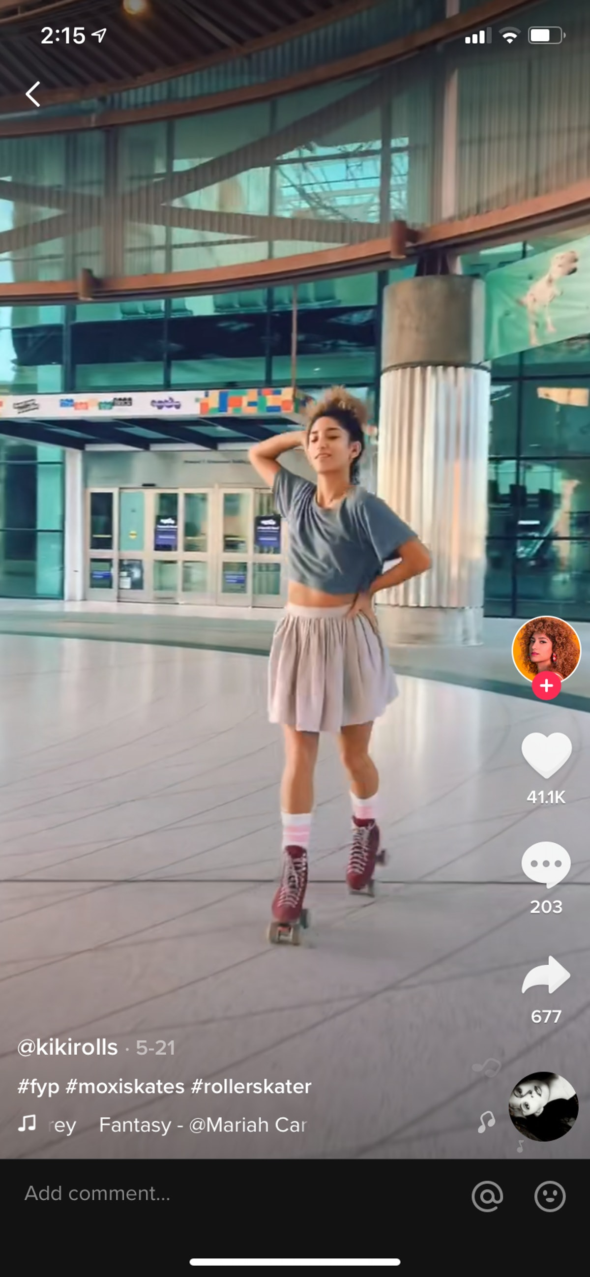 A young Black woman roller skates near a movie theater and poses for a TikTok video.