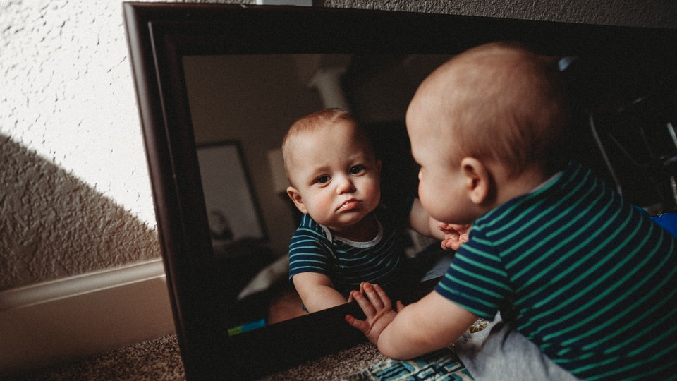 A baby looks at his reflection in a mirror.