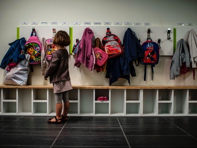 little girl putting backpack away at her cubby, preschool