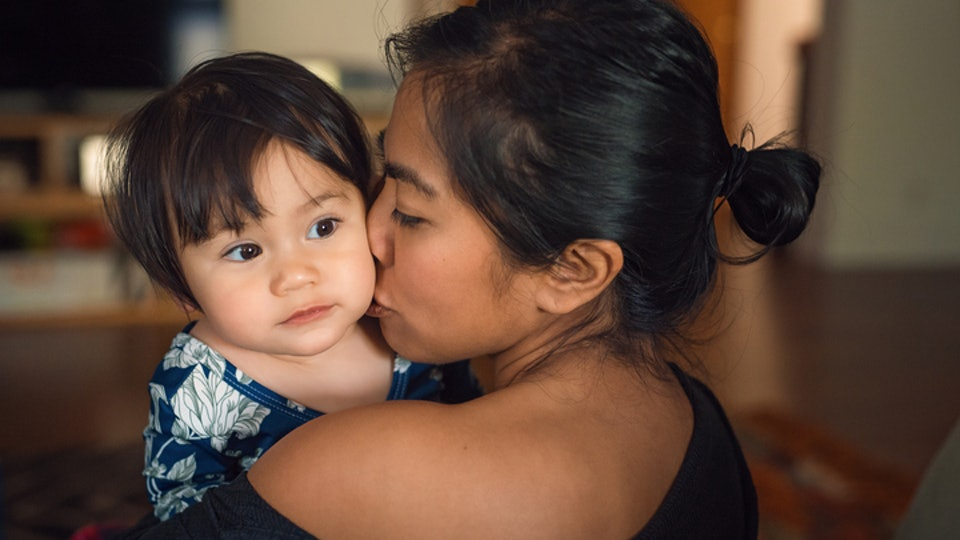 mother holding toddler child, kissing on the cheek