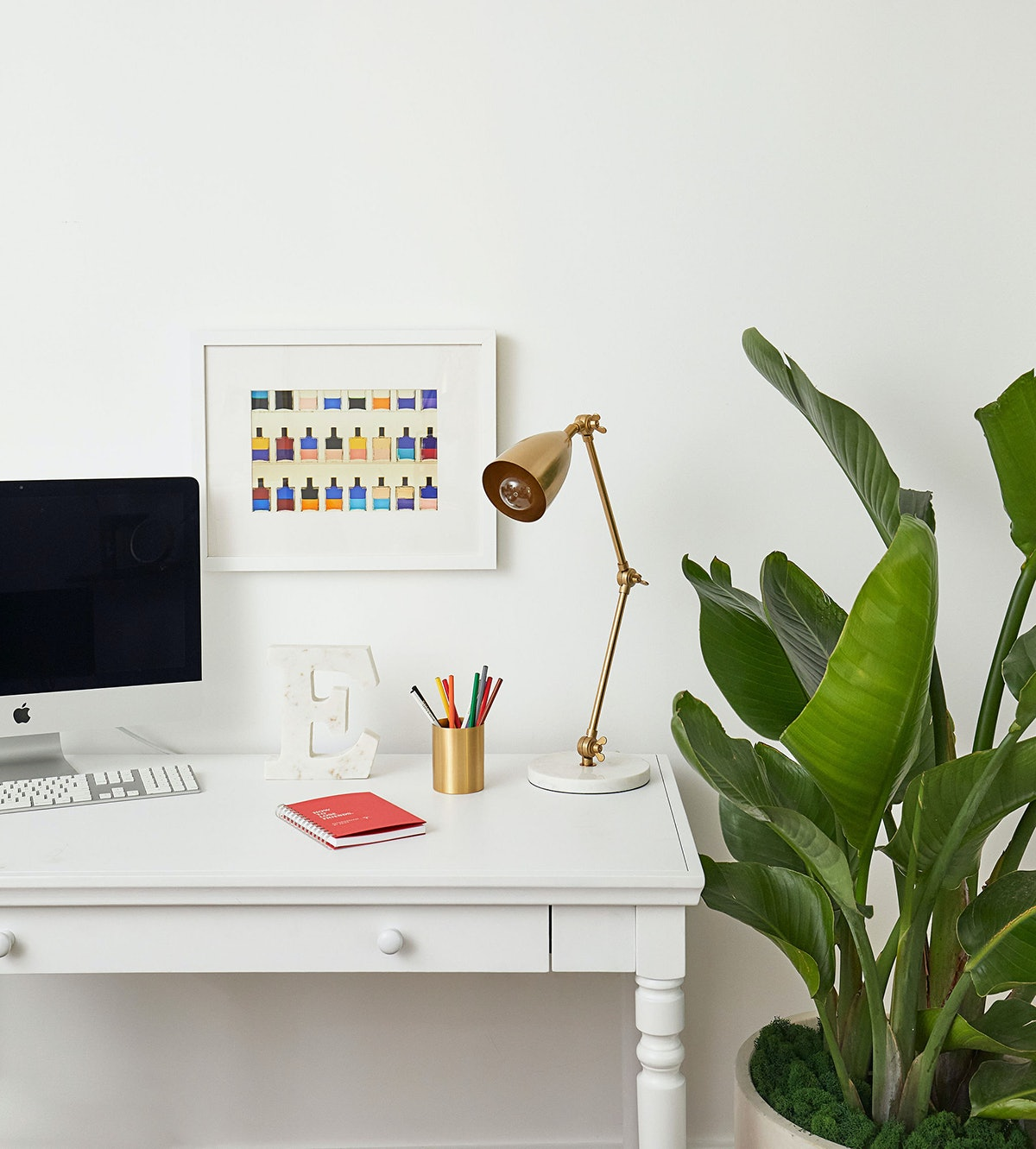 """A remote learning set-up features a minimalistic desk, gold lamp, computer, and plants, created with Bed Bath & Beyond's """"College from Home"""" experience."""