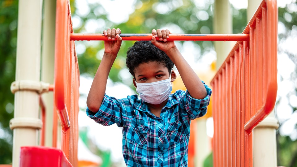 A boy wearing a mask sits on playground equipment.