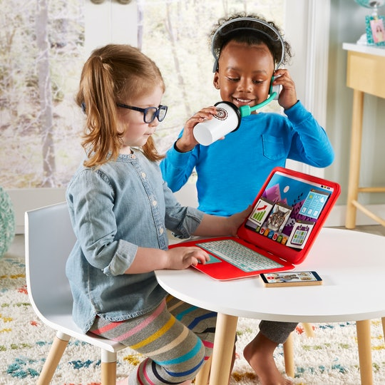 A picture of a little girl with striped leggings and chambray shirt sitting at a desk with a toy laptop while a little boy in a blue shirt looks on with his toy coffee cup and headset.