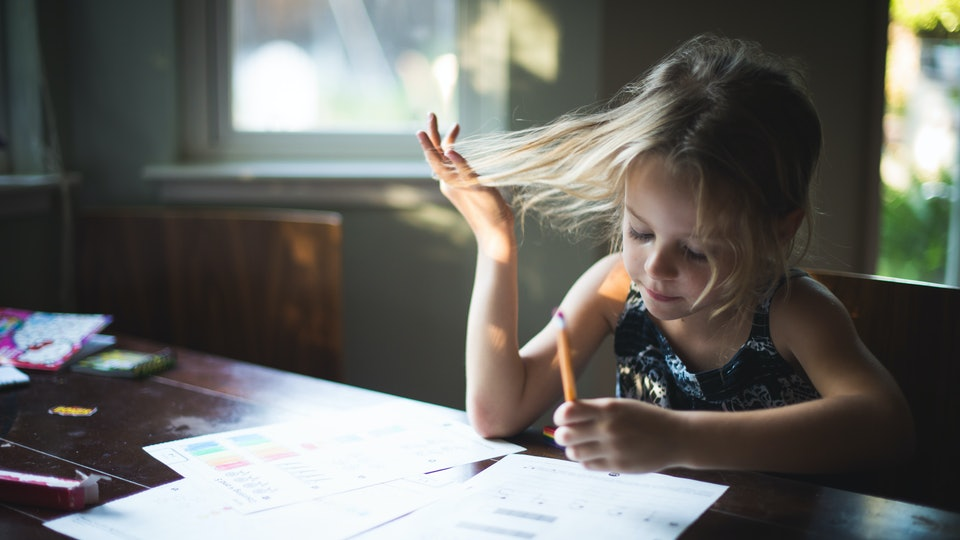 A girl plays with her hair while doing homework