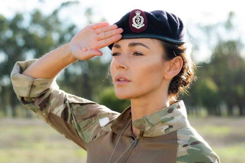 Michelle Keegan as Sgt Georgie Lane wearing army fatigues and a beret with her arm raised in a salute