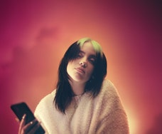 Billie Eilish looks at the camera, one hand holding a smartphone.