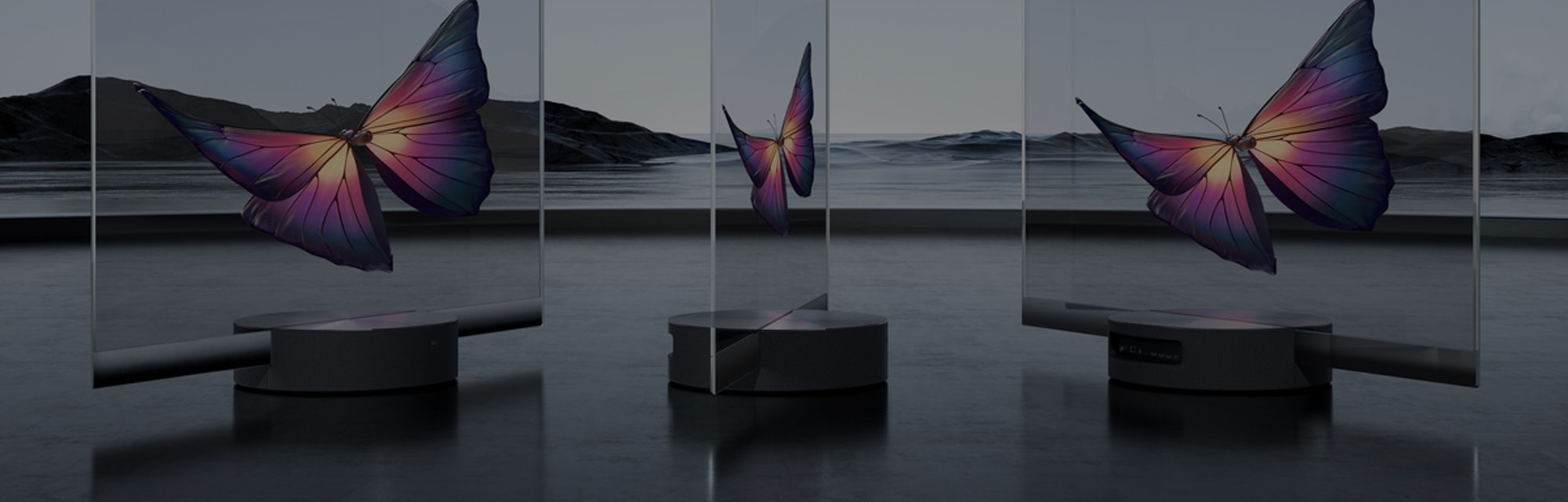 The world's first mass-produced TV by Xiaomi can be seen. The screens are transparent while there are deep purple butterflies seen inside. The background is minimalist depicting serene water and a few rocky hills.