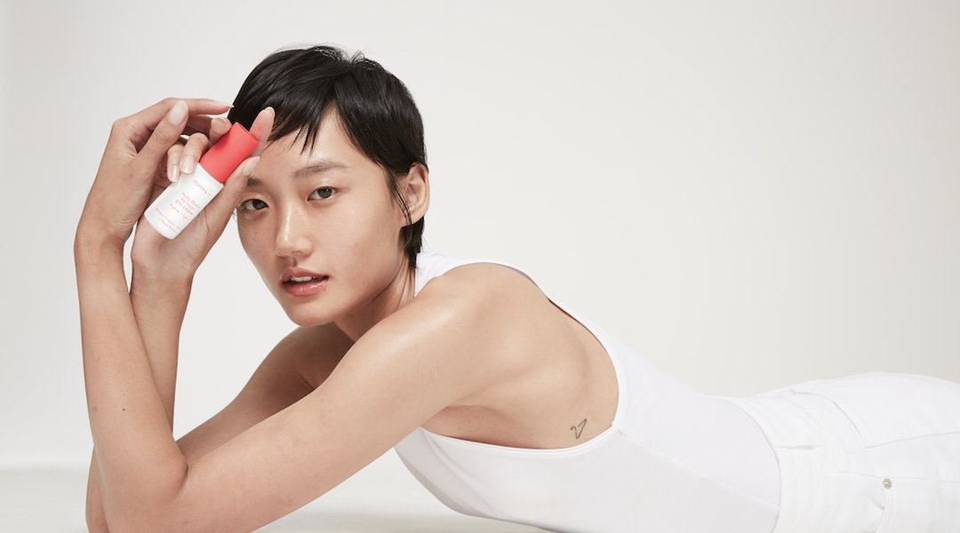 Peach & Lily's new Pure Peach Retinoic Eye Cream held by model.