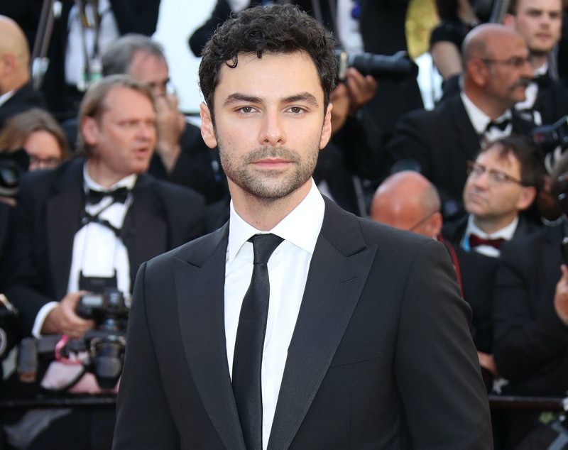 Aidan Turner wearing a suit at a premier with paparazzi in the background