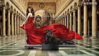A see-through TV set by Xiaomi can be seen showing a black panther in reclining position. A model is behind the screen in a deep red satin dress. The background depicts large marble pillars and block designs on the floor