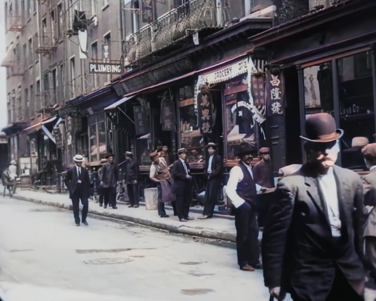 AI-restored footage can be seen of an old clip from New York City in 1911. A man with a mustache is walking down the street while other pedestrians can be seen roaming in the market.