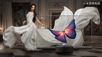 A model in a white dress is seen behind a transparent Xiaomi TV screen. The model can be seen in an opulent-looking lounge with checkers floor. The screen shows a deep purple, blue, and orange butterfly suspended mid-air.
