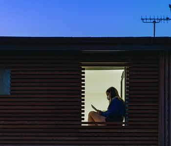 Teenage girl sitting in her window at home.