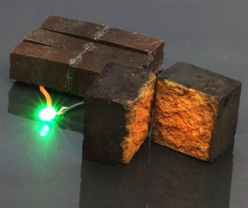 Three red bricks can be seen. A green LED light emerges from one of them, fully lit without any other energy source except the building blocks.