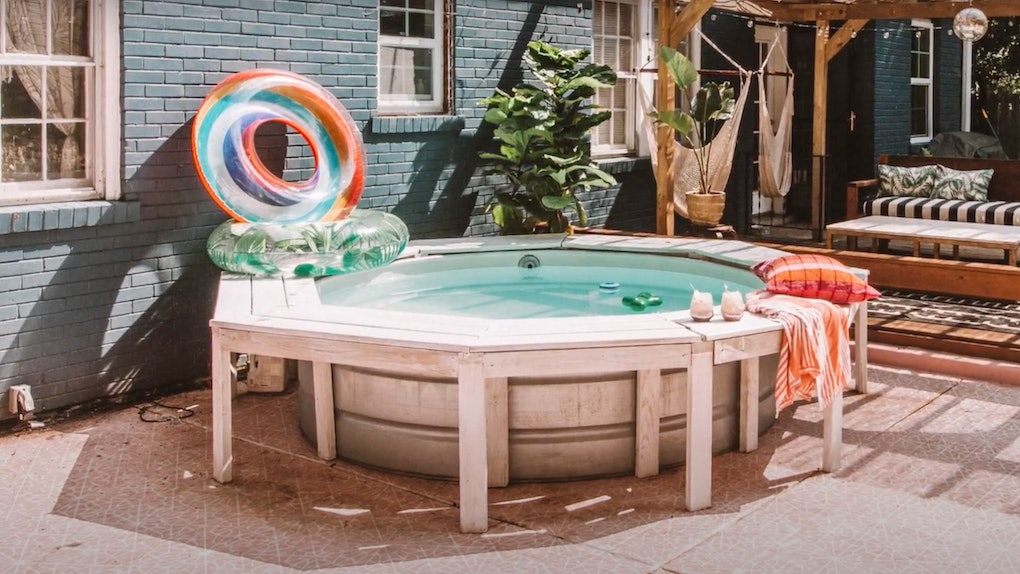 A decorated stock tank pool sits in the backyard with pool floats and cocktails.